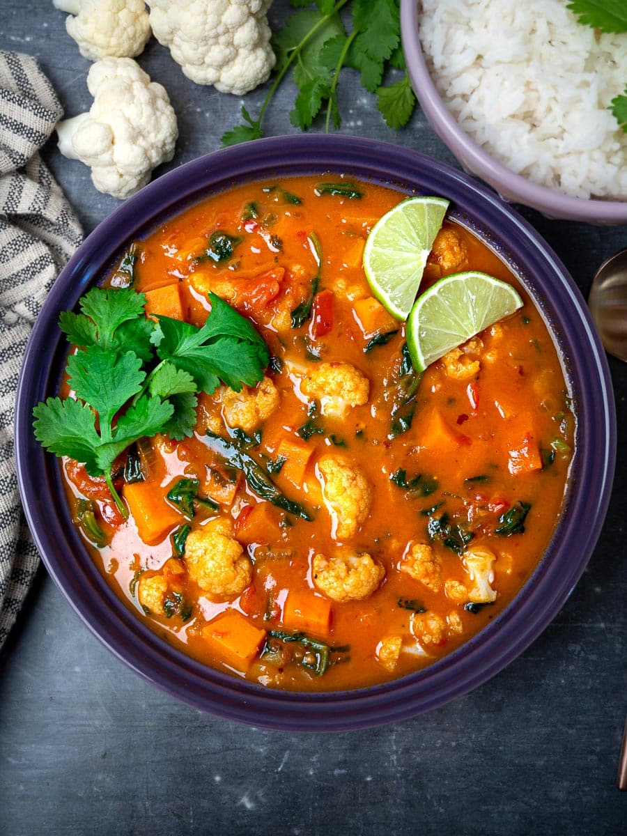 A bowl of cauliflower curry with rice on the side