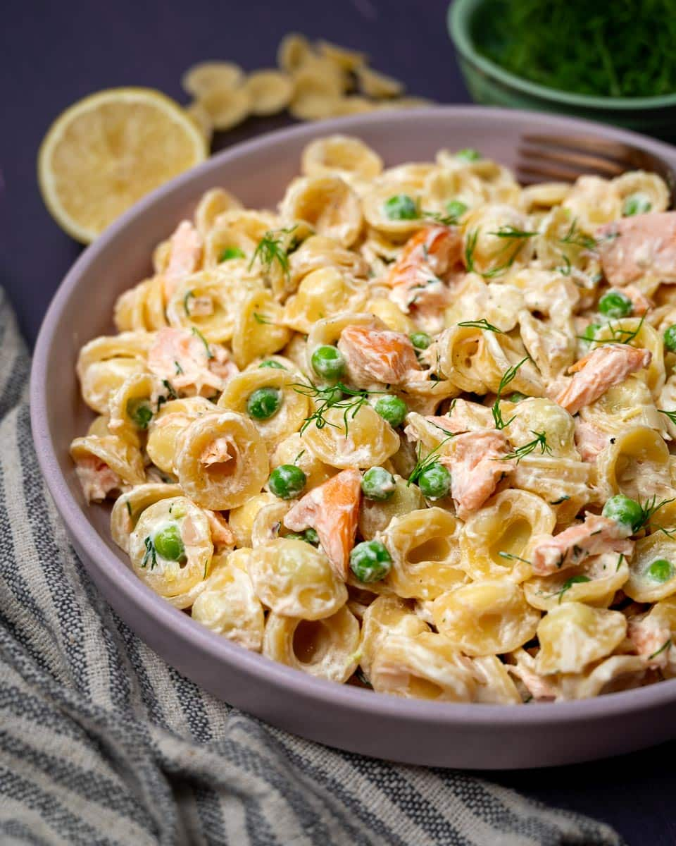 A plate of hot smoked salmon pasta with peas and dill
