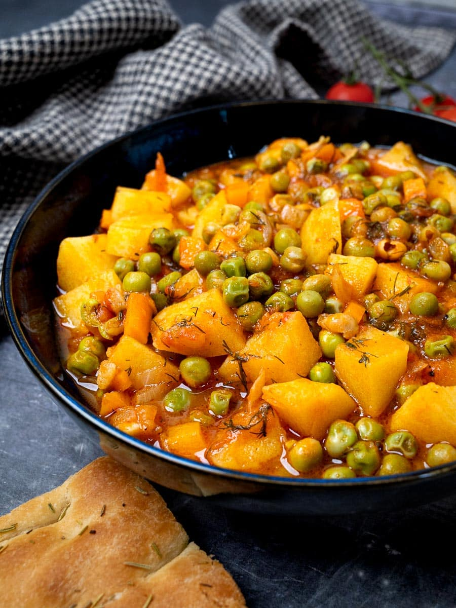 A bowl of pea and potato stew with bread on the side