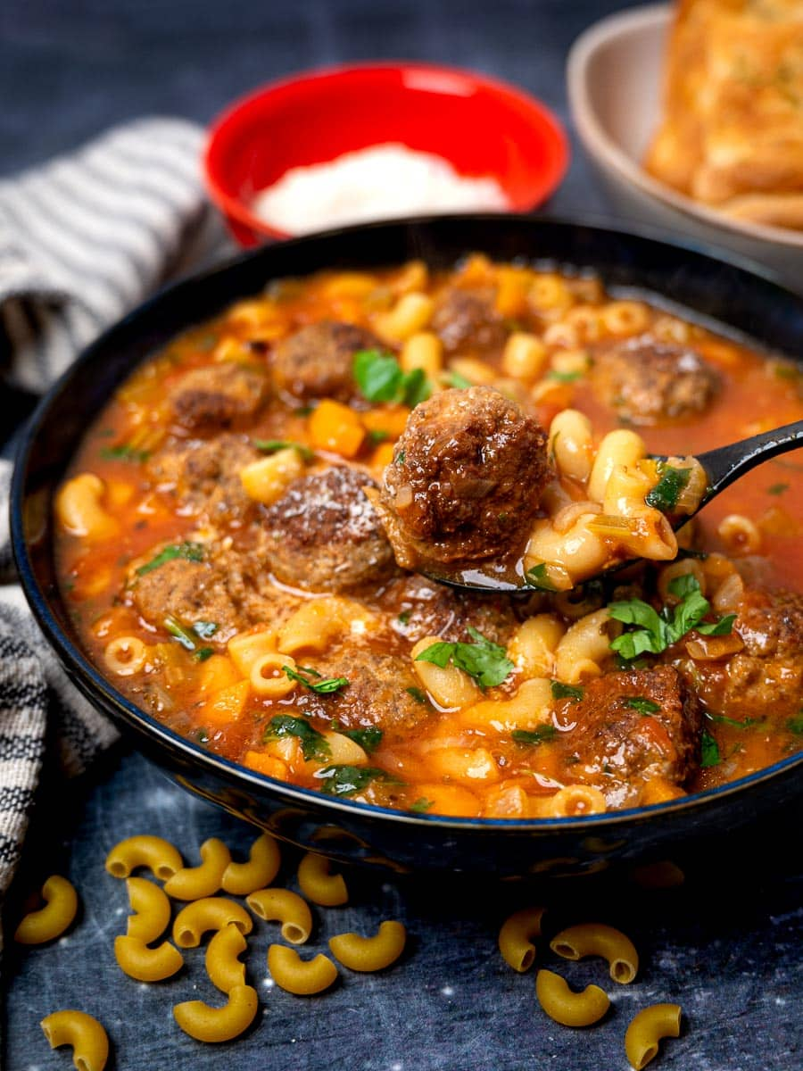 Close up photo of a bowl of Italian meatball soup with a spoon in