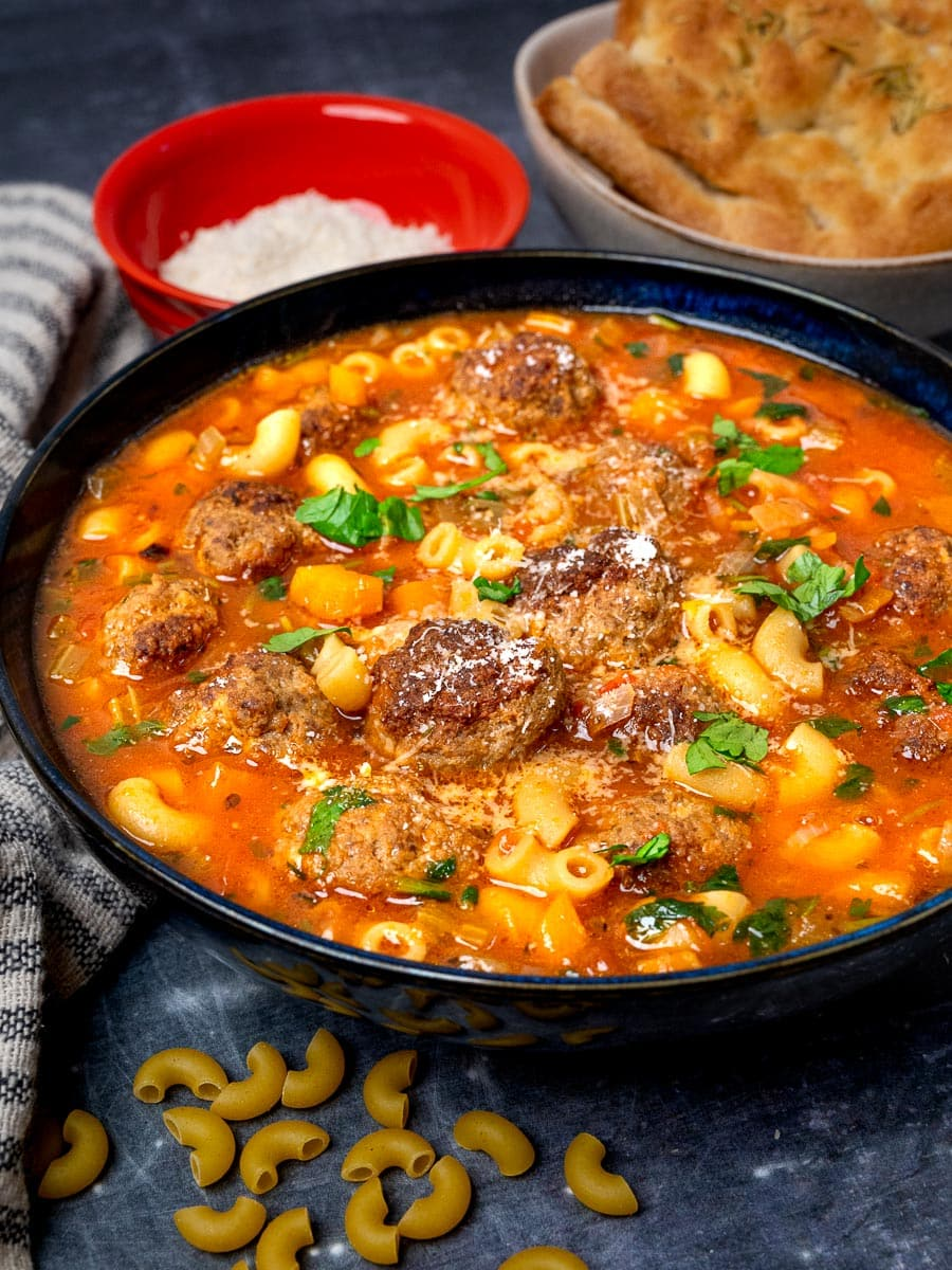 A bowl of tomato soup with pasta and meatballs with bread on the side