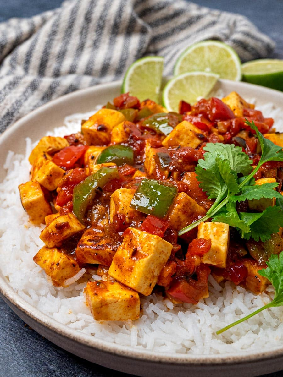 A plate of paneer jalfrezi and rice with lime wedges on the side