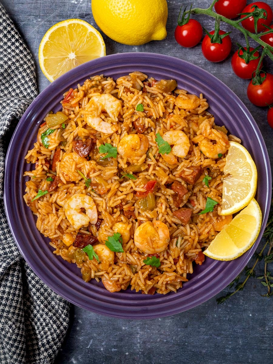 A bowl of jambalaya with lemon and cherry tomatoes on the side